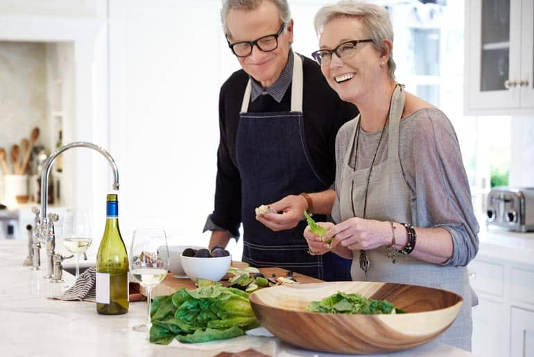 older woman with dentures cooks up a delightful meal
